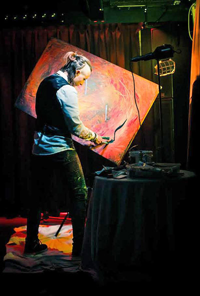 Sarah Rowan using her artristic easel to paint on a rotating canvas at a fundraising event in Australia