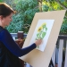 Artist painting with art board attached to artristic easel using board supports